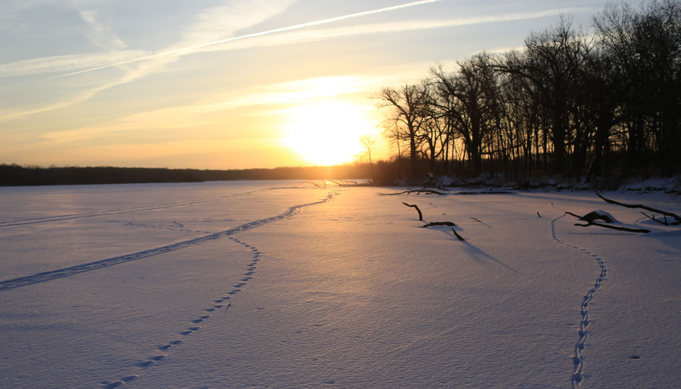 sun rising over a frozen lake covered in snow