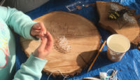 a person using string, nails and a slice of tree trunk to make art at Rolling Knolls Pavilion