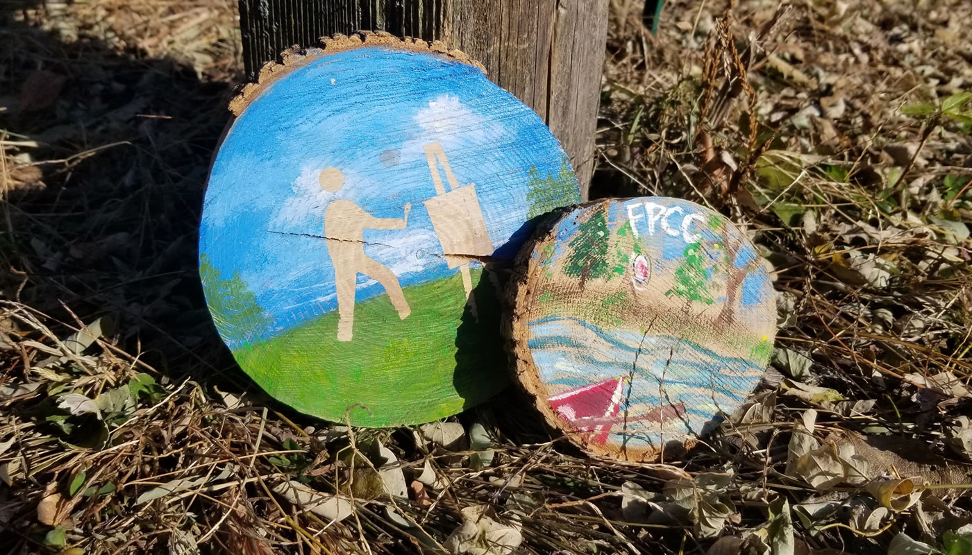 two painted tree trunk slices leaned up against a post at Sand Ridge Nature Center