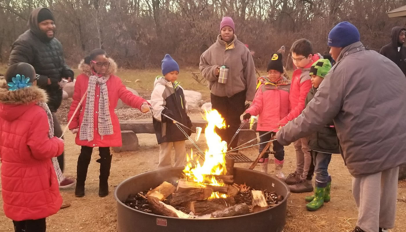 a group cooking over a campfire at Camp Shabbona Woods