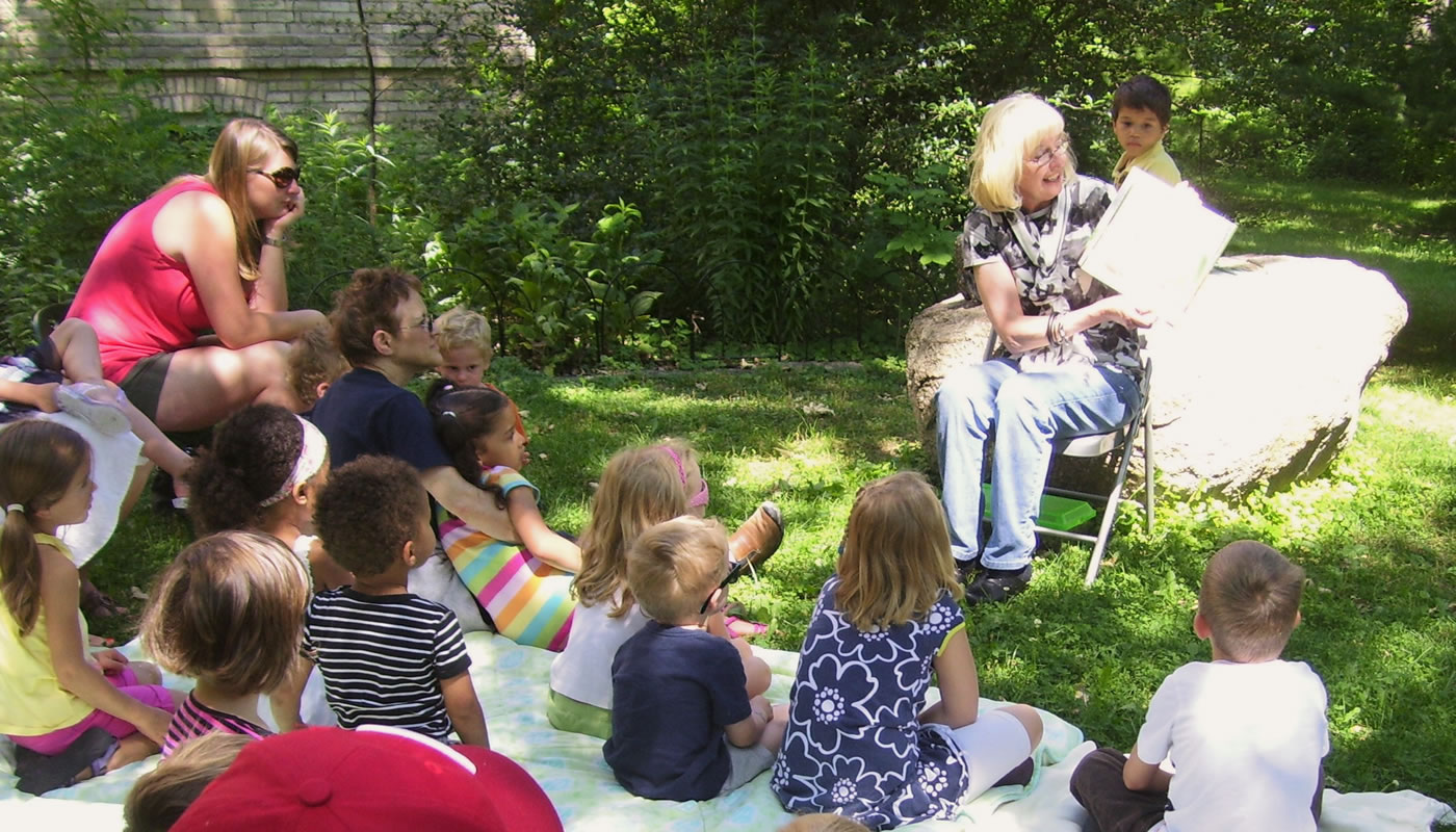 a Forest Preserves staff member reading a story to a group of children at Trailside Museum