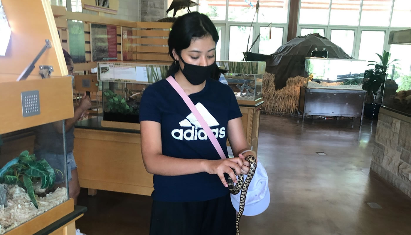 Leslye Carrasco with a snake at Little Red Schoolhouse