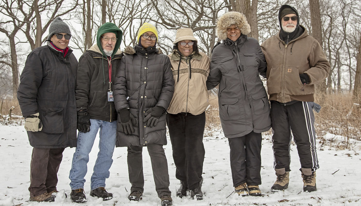 A group of volunteers gathered at Kickapoo Woods, smiling, for a photo
