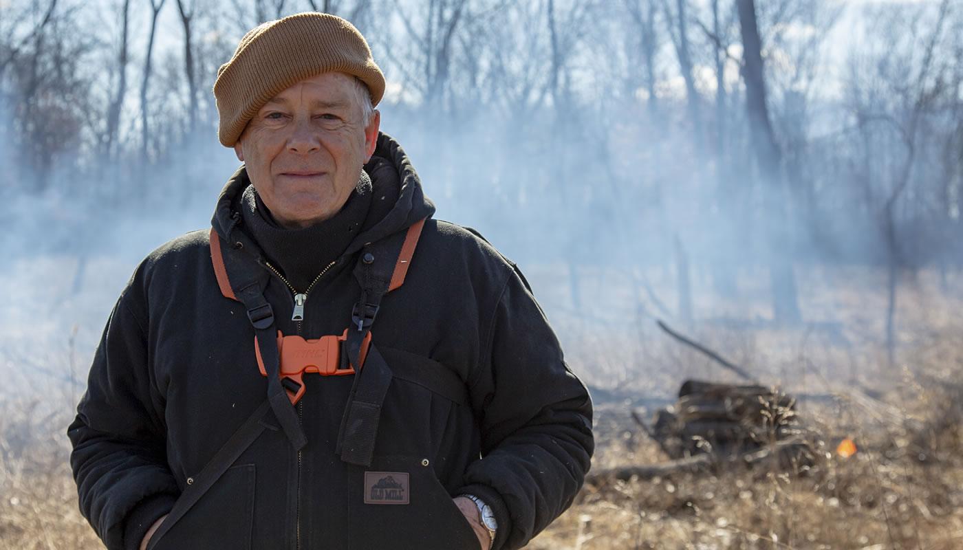 Dennis Kankowske volunteering at Sundown Meadow in front of a brush pile.