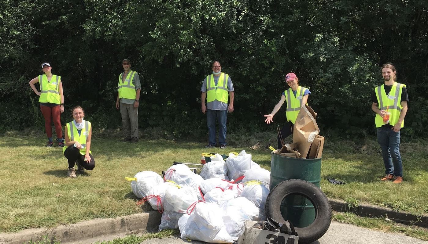 a group of volunteers standing around the trash they collected from the forest preserves