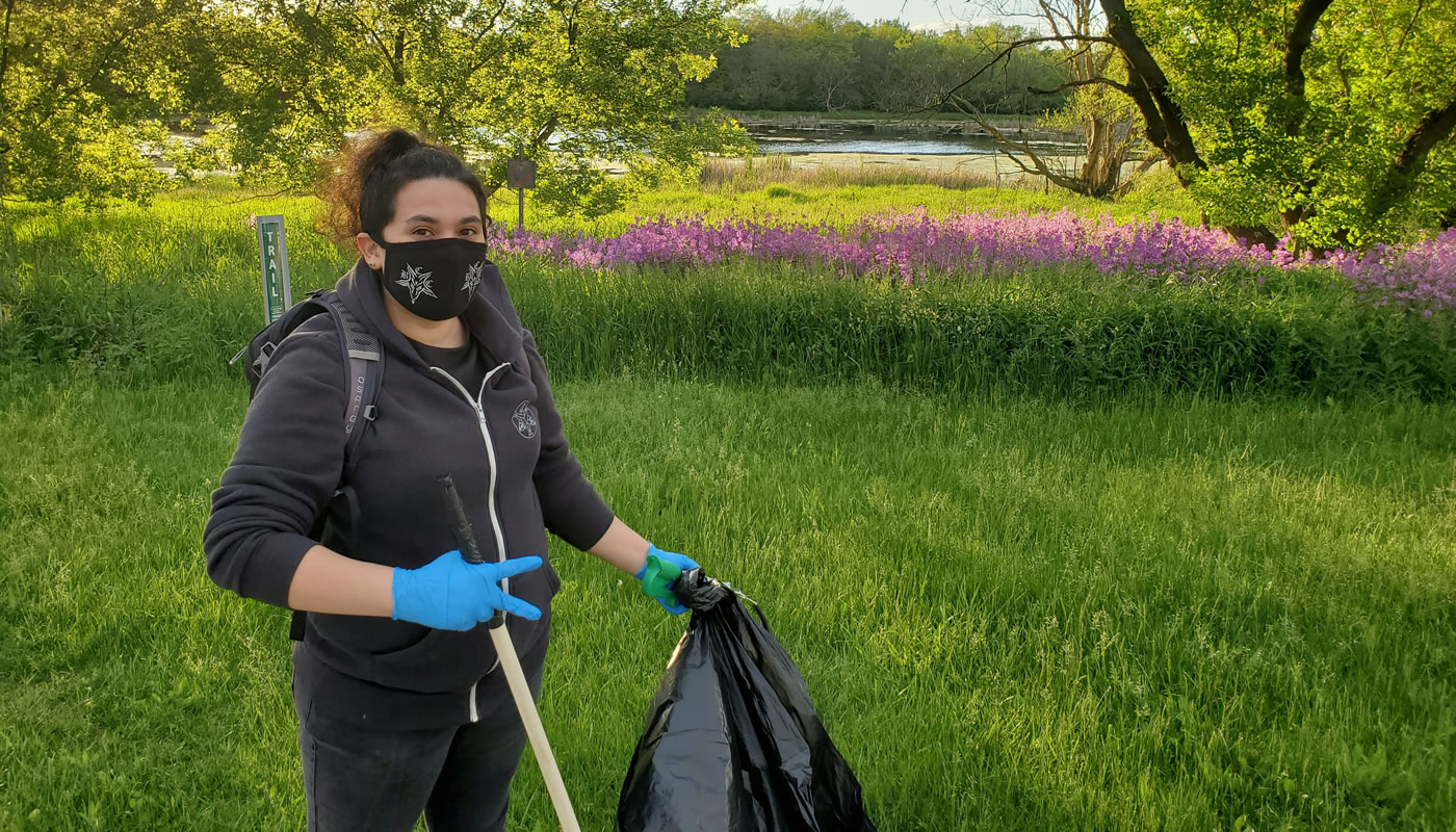 a volunteer picking up trash near a pond in the forest preserves