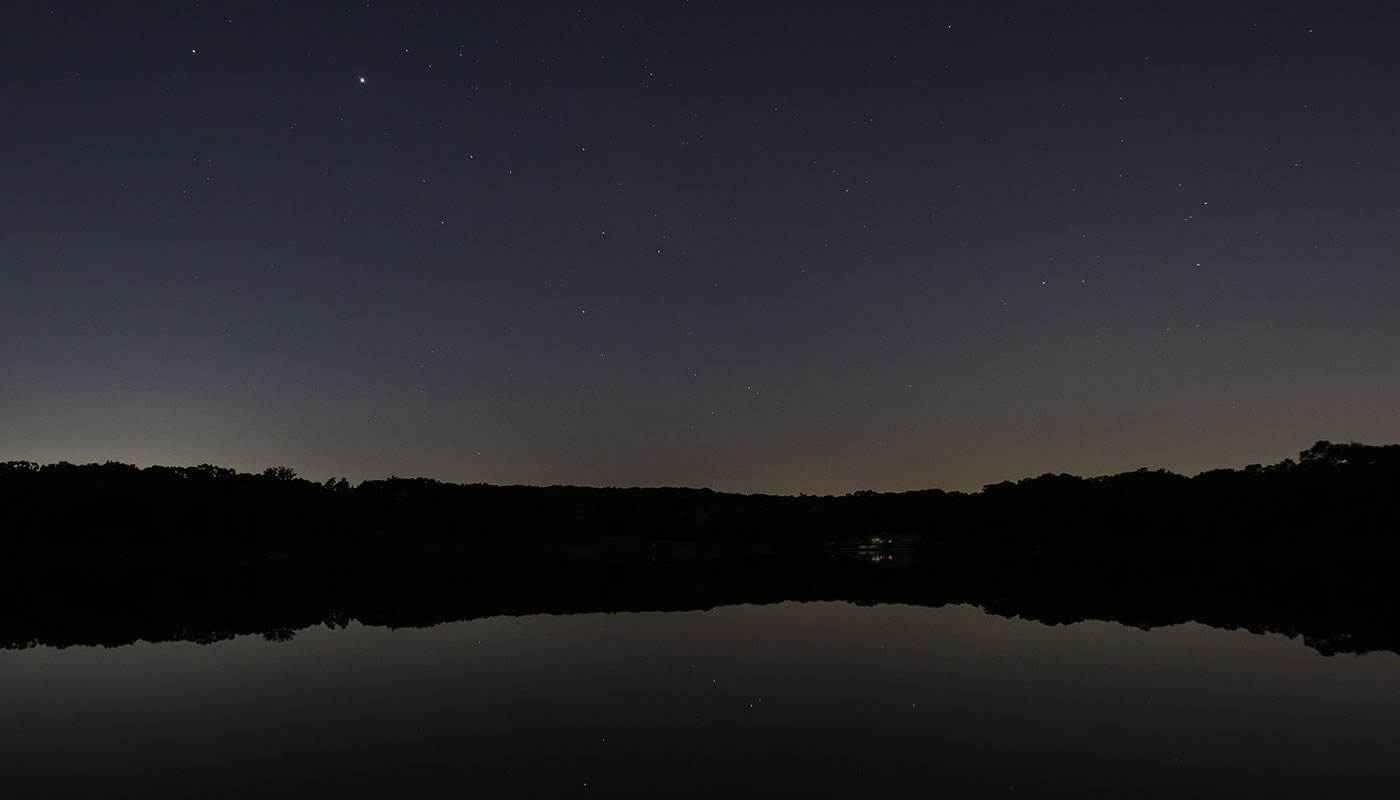 view of Maple Lake at night with stars in the sky and reflecting on the water