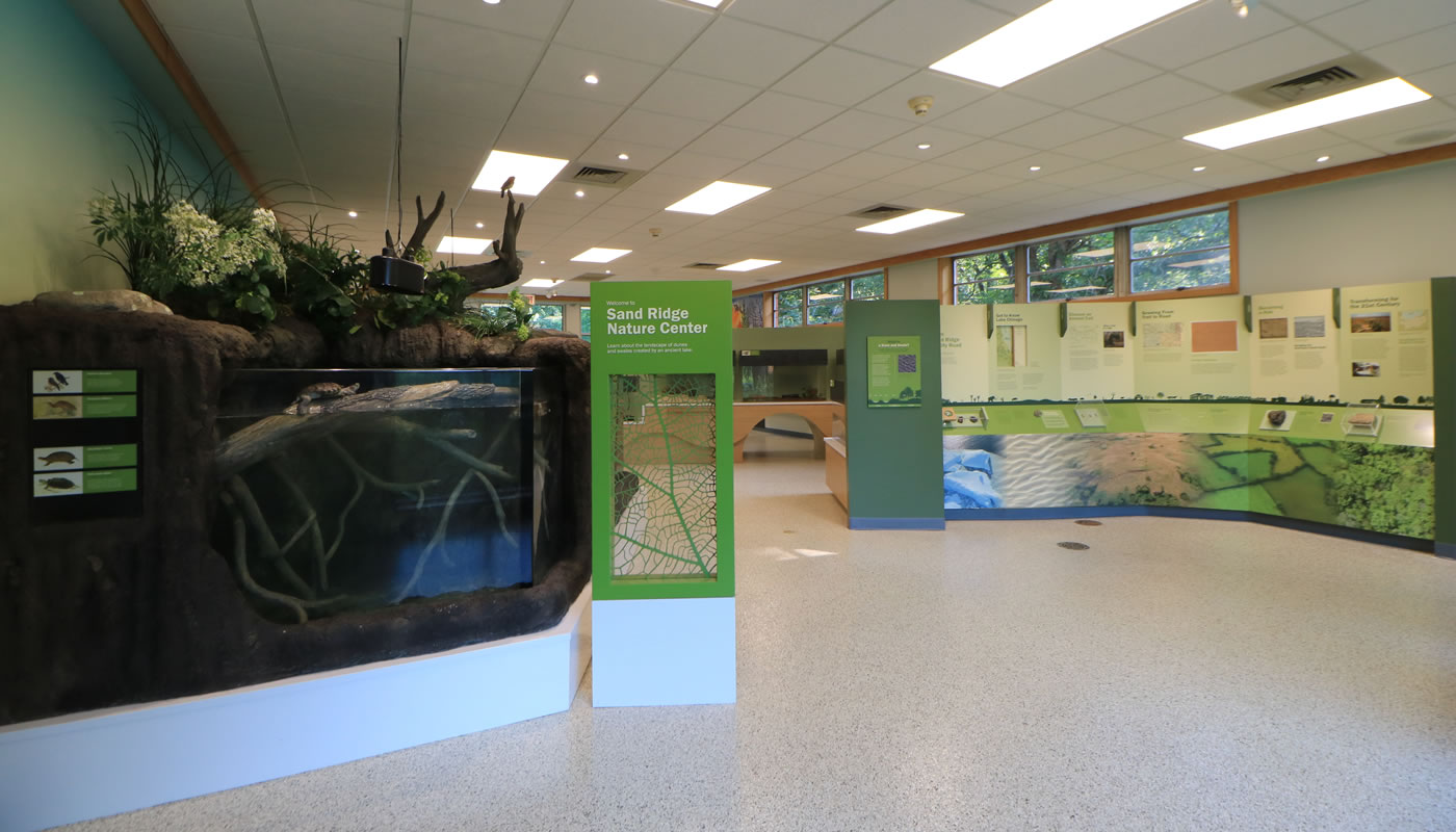 inside the Sand Ridge Nature Center exhibit room showing educational exhibits and turtles